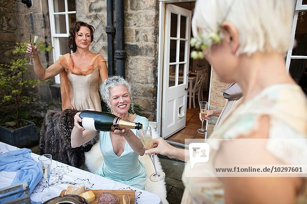 Elegant mature women enjoying champagne in urban garden
