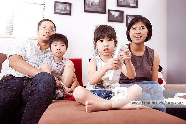 Junge  moderne chinesische Familie von Eltern und zwei kleinen Kindern  die gemeinsam zu Hause auf dem Sofa sitzen und fernsehen.