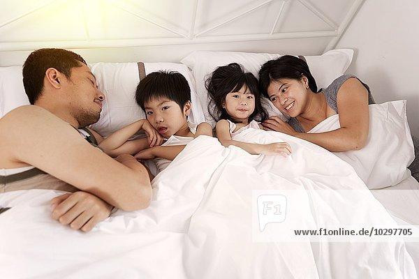 Junge chinesische Elternfamilie und zwei kleine Kinder  die zu Hause zusammen im Bett liegen