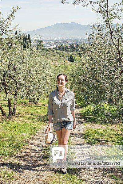Durchgehende Vorderansicht einer jungen Frau  die auf einem Feldweg läuft und lächelnd davonschaut.