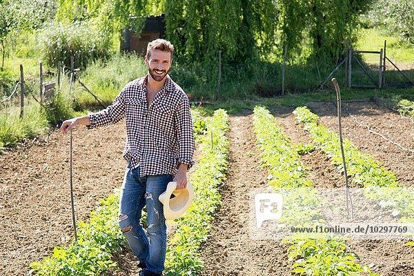 Junger Mann mit Hut im Gemüsegarten stehend und lächelnd in die Kamera schauend Junger Mann mit Hut im Gemüsegarten stehend und lächelnd in die Kamera schauend
