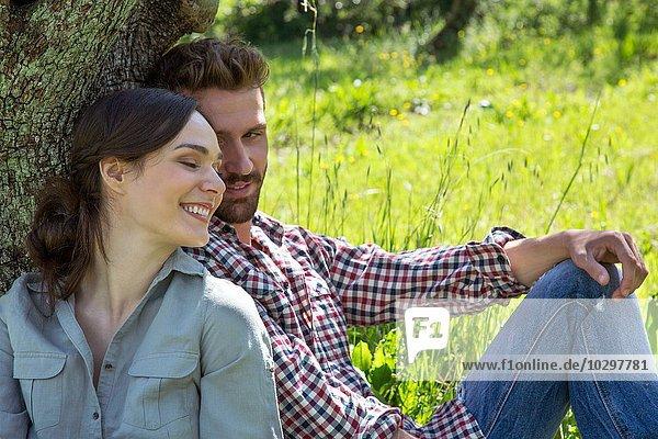 Junges Paar  das zusammen an einen Baum gelehnt sitzt. Junges Paar, das zusammen an einen Baum gelehnt sitzt.