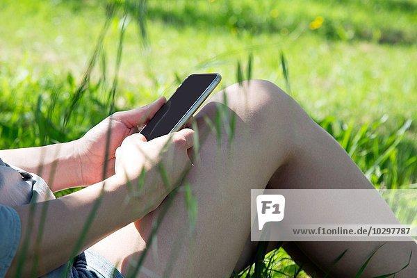 Ausschnitt einer jungen Frau mit Smartphone Ausschnitt einer jungen Frau mit Smartphone