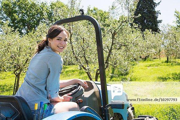 Junge Frau sitzt im Traktor und schaut über die Schulter  lächelnd auf die Kamera. Junge Frau sitzt im Traktor und schaut über die Schulter, lächelnd auf die Kamera.