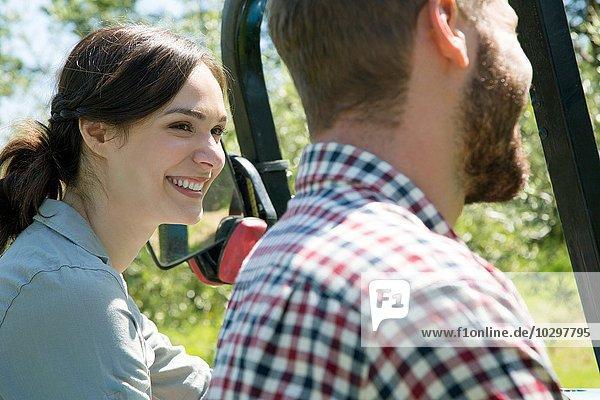 Seitenansicht von lächelnden jungen Paaren Kopf und Schultern mit Traktor Seitenansicht von lächelnden jungen Paaren Kopf und Schultern mit Traktor