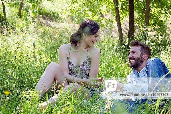 Junges Paar liegt auf Gras und isst Erdbeeren lächelnd. Junges Paar liegt auf Gras und isst Erdbeeren lächelnd.
