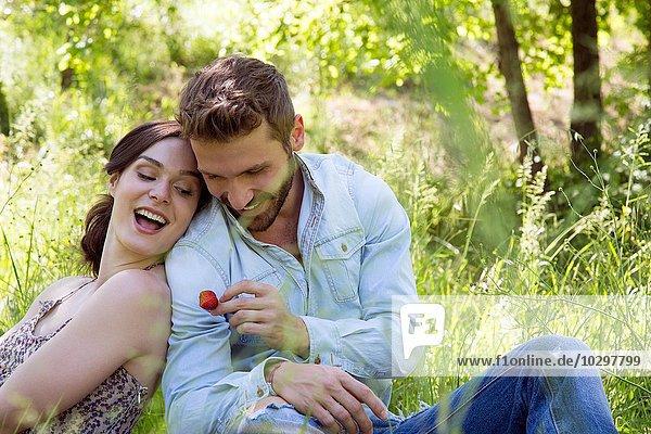 Junges Paar sitzt Rücken an Rücken auf Gras und hält Erdbeere lächelnd.