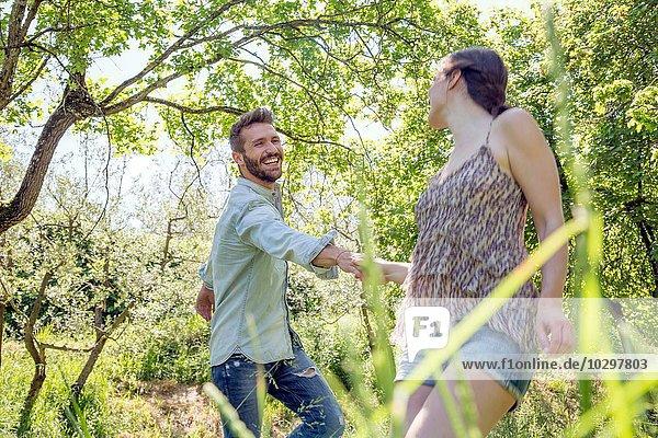 Junges Paar  das im Wald Händchen hält und lächelnd herumalbert. Junges Paar, das im Wald Händchen hält und lächelnd herumalbert.