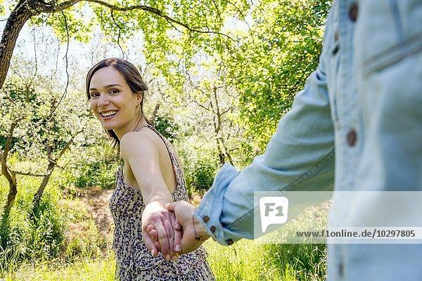 Junge Frau führt jungen Mann durch den Wald  hält die Hand Junge Frau führt jungen Mann durch den Wald, hält die Hand