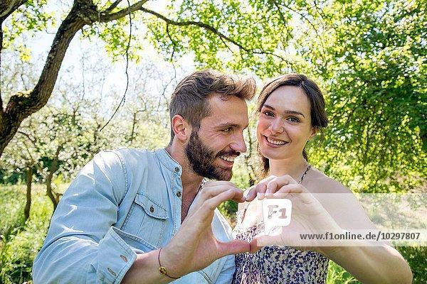 Junges Paar  das mit Händen das Herz in Form bringt  lächelnd in die Kamera schaut.