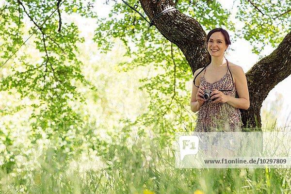 Junge Frau  die sich gegen einen Baum lehnt und die Kamera hält und lächelnd wegsieht. Junge Frau, die sich gegen einen Baum lehnt und die Kamera hält und lächelnd wegsieht.
