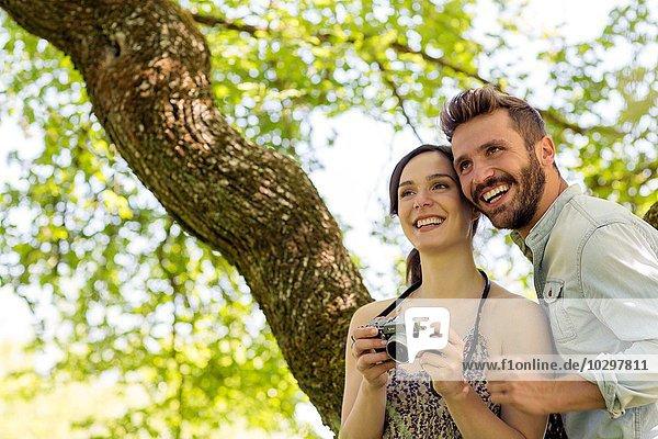 Junges Paar unter dem Baum hält die Kamera und schaut lächelnd weg. Junges Paar unter dem Baum hält die Kamera und schaut lächelnd weg.