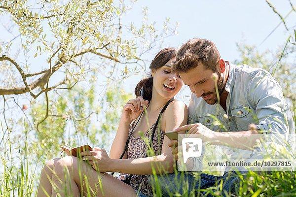 Niedriger Blickwinkel auf ein junges Paar  das auf ein lächelndes Smartphone blickt.