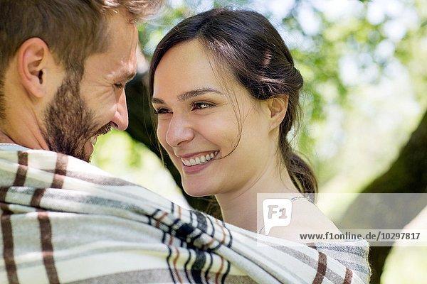 Kopf und Schultern eines jungen Paares in eine Decke gewickelt  von Angesicht zu Angesicht lächelnd. Kopf und Schultern eines jungen Paares in eine Decke gewickelt, von Angesicht zu Angesicht lächelnd.