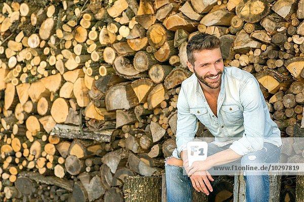 Junger Mann vor gehacktem Holz sitzend Junger Mann vor gehacktem Holz sitzend