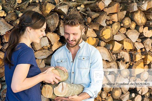 Junges Paar  das gehacktes Brennholz vom Stapel auswählt Junges Paar, das gehacktes Brennholz vom Stapel auswählt