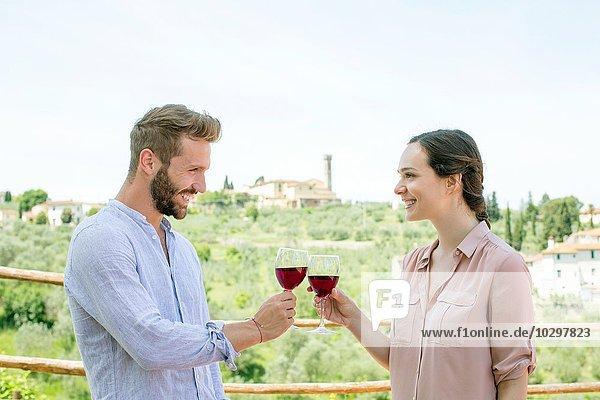 Taille oben Seitenansicht des jungen Paares von Angesicht zu Angesicht  das einen Toast lächelt. Taille oben Seitenansicht des jungen Paares von Angesicht zu Angesicht, das einen Toast lächelt.