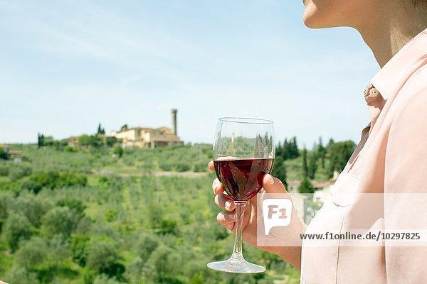 Ausschnitt einer jungen Frau  die ein Weinglas in der Hand hält und wegschaut. Ausschnitt einer jungen Frau, die ein Weinglas in der Hand hält und wegschaut.