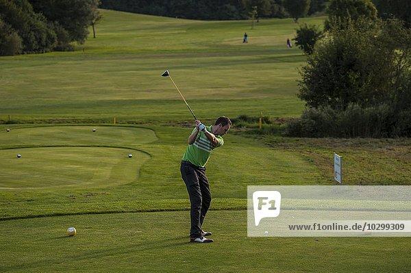 Golfer bei Abschlag auf dem Golfplatz  Bayern  Deutschland  Europa