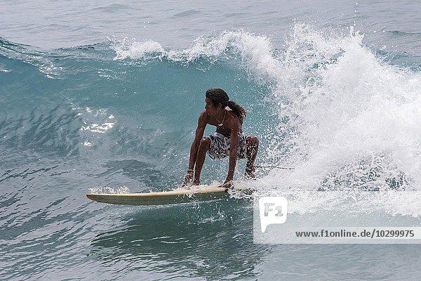 Einheimischer junger Mann reitet mit dem Surfbrett auf den Wellen  Wellenreiter  Anse Patates  Indischer Ozean  Insel La Digue  Seychellen  Afrika