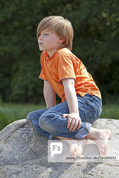 Boy sitting on rock  Germany  Europe