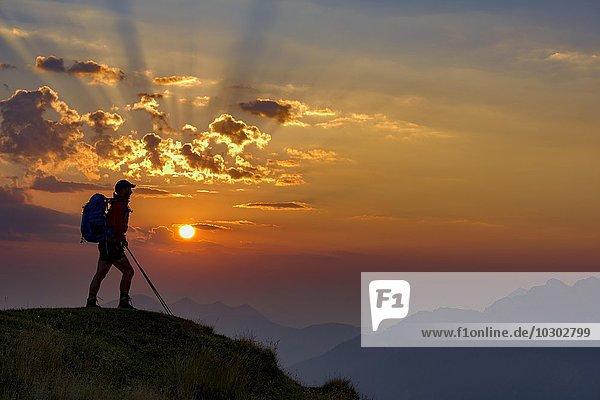 Bergsteiger im Gegenlicht bei Sonnenaufgang mit Bergen  Estergebirge  Ettal  Oberbayern  Bayern  Deutschland  Europa