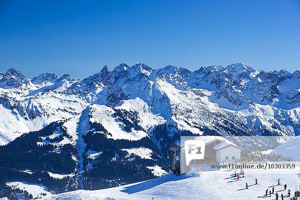 Skifahrer an der Ifenbahn im Winter  Bergstation der Hahnenköpflebahn  Gottesackerplateau  Kleinwalsertal  Vorarlberg  Österreich  hinten Allgäuer Hauptkamm  Bayern  Deutschland  Europa