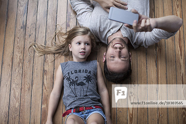 Kleines Mädchen und Vater liegen zusammen auf dem Boden und schauen auf das Smartphone.