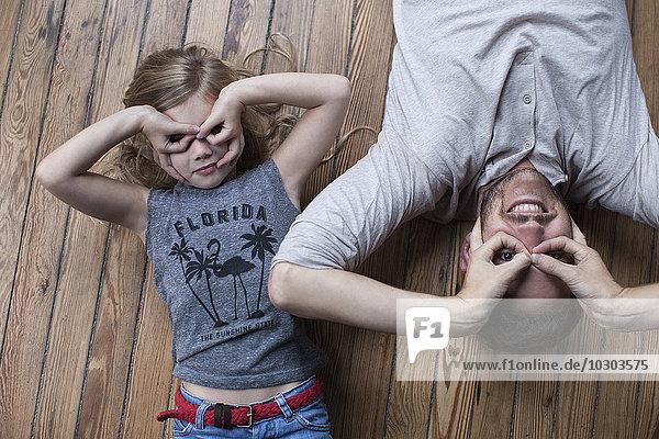 Kleines Mädchen und Vater machen Gesichter