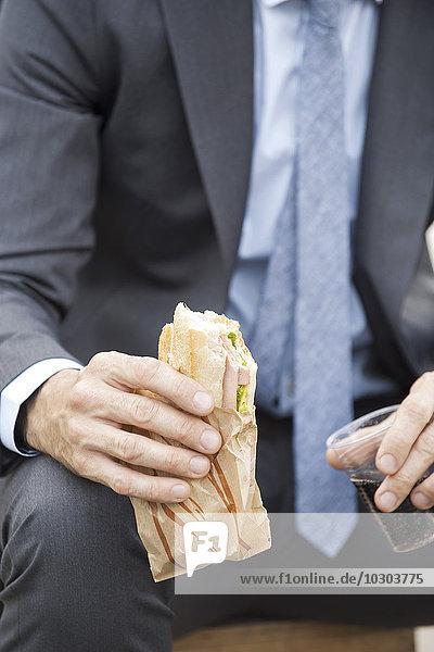 Geschäftsmann mit Sandwich  beschnitten