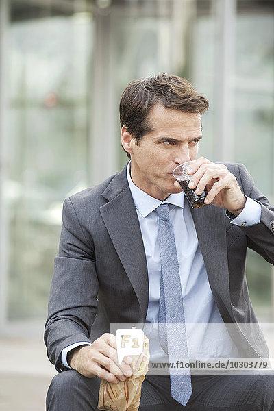 Geschäftsmann beim Mittagessen im Freien