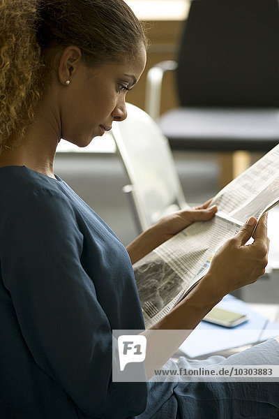 Woman reading newspaper in waiting room