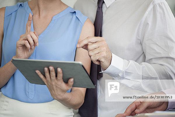 Geschäftskollegen  die mit digitalem Tablett arbeiten  beschnitten