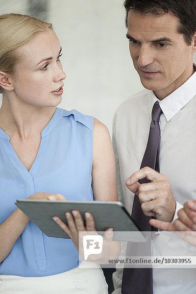 Geschäftspartner  die gemeinsam ein digitales Tablett verwenden