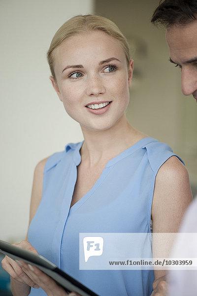 Geschäftsfrau zeigt digitales Tablett dem Kollegen