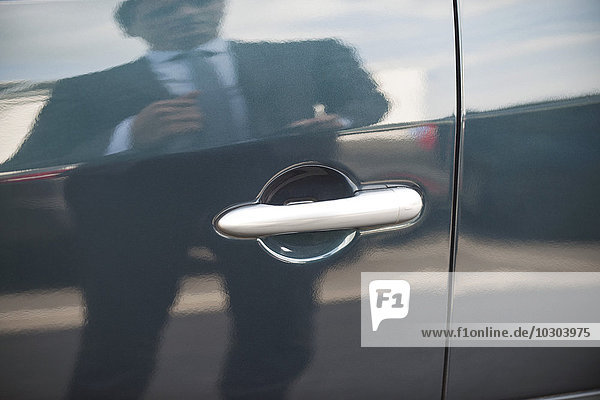 Geschäftsmann reflektiert an der Autotür