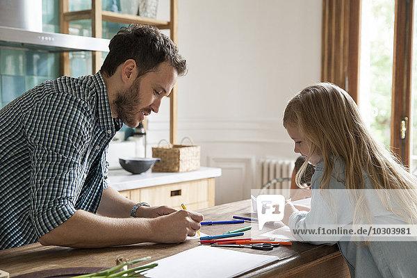 Vater und Tochter zeichnen zu Hause
