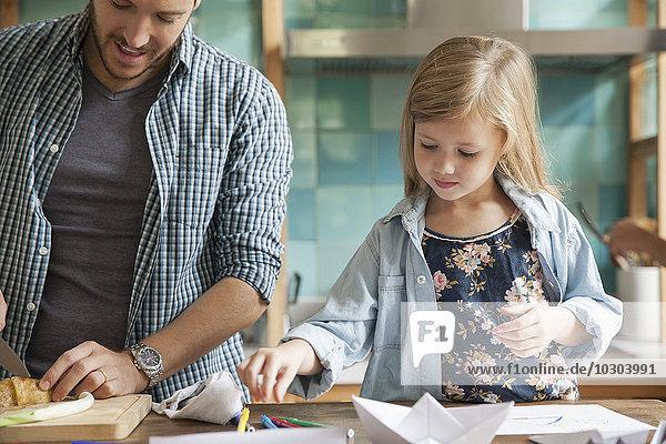 Kleines Mädchen malt in der Küche  während die Familie das Essen zubereitet.