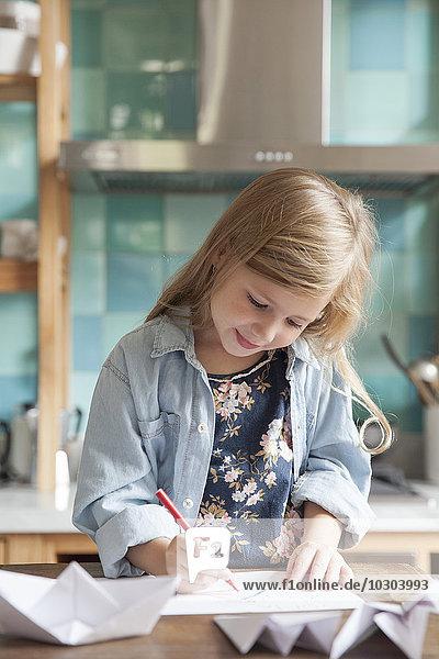 Kleines Mädchen beim Zeichnen in der Küche  Portrait