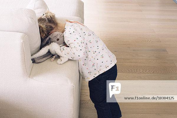Kleines Mädchen versteckt ihr Gesicht in Sofakissen