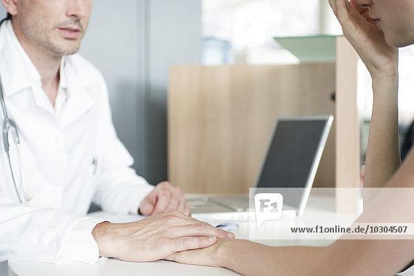Arzt tröstender Patient nach der Lieferung von schlechten Nachrichten  abgeschnitten