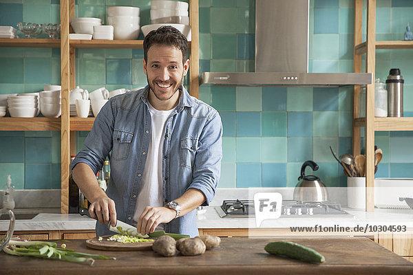 Mann schneidet Zutaten in der Küche  Porträt