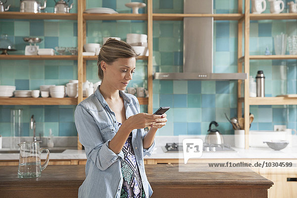 Junge Frau steht in der Küche mit Handy