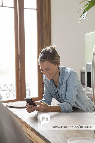Junge Frau mit Smartphone in der Küche
