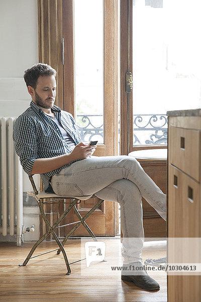 Mann mit Smartphone zu Hause