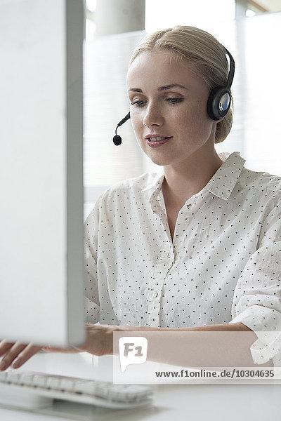 Frau mit Desktop-Computer und Headset im Büro