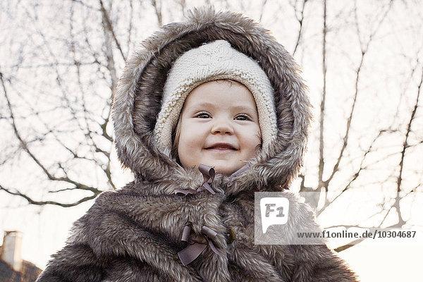 Baby girl wearing fur coat outdoors  portrait