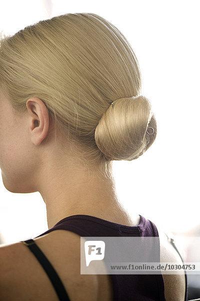 Frau mit in einem Chignon angeordneten Haaren