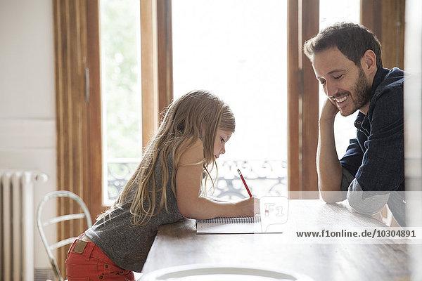 Vater hilft Tochter beim Schreiben