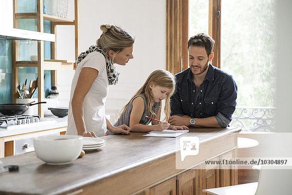 Eltern helfen der kleinen Tochter beim Unterricht